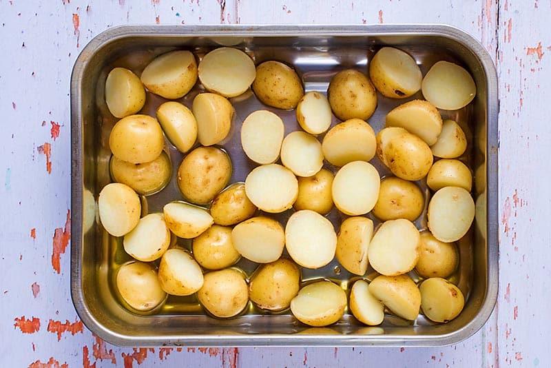 A roasting tin full of halved new potatoes