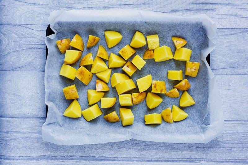 Cubes of potato laid out on a lined baking tray.