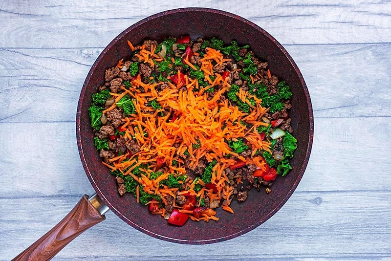 A frying pan with pepper, onion, garlic, carrot, kale and ground beef.