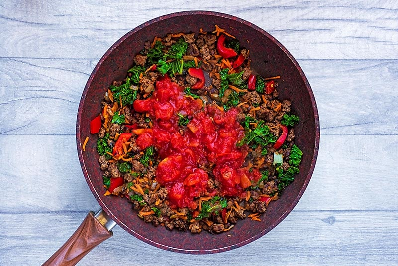 Grounf beef and vegetables cooking in a pan with chopped tomatoes.