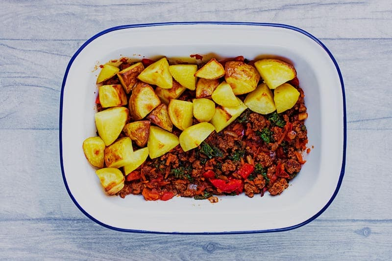 A baking dish filled with beef and vegetables and half topped with potatoes.